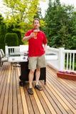 Man att tycka om kallt öl, medan förbereda sig att laga mat utomhus Royaltyfri Fotografi