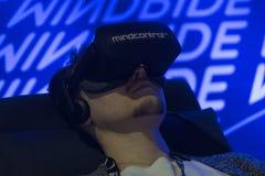 Man att tycka om virtuell verklighetexponeringsglas, medan koppla av på soffan Fotografering för Bildbyråer