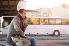 Man att vänta på bussstationen och samtal på mobiltelefonen royaltyfria bilder