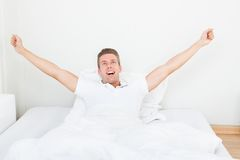Man att vakna upp i morgon och sträckning på säng Royaltyfria Foton