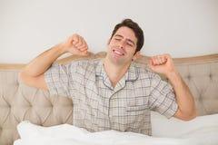 Man att vakna upp i säng och sträckning av hans armar Arkivbild