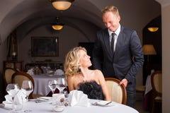 Man att vara en gentleman och en hjälpande kvinna med hennes stol Arkivfoton