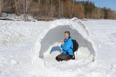 Man att vila i oavslutat en igloo på en glänta royaltyfri bild