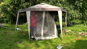 Man attach protective tent bower net in garden stock video