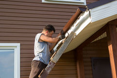 Man attaches gutter on roof of porch Stock Image