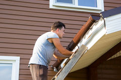 Man attaches gutter on roof of the porch Stock Image