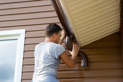 Man attaches gutter on roof of the porch Royalty Free Stock Photo