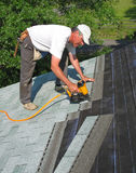 Man attaches shingles to roof Stock Photos