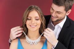 Man attaching necklace to girl's neck. Stock Images