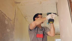 Man attaching plank with drill. Side view of man in glasses using electric drill and fixing plank on bare wall in empty room, slow motion stock footage