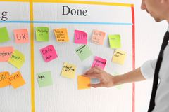 Man attaching sticky note to scrum task board in office stock photo