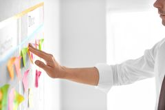 Man attaching sticky note to scrum task board in office stock images