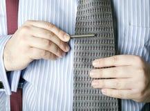 Man attaching tie clip to necktie Royalty Free Stock Photos