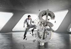 Man attacking dollar symbol. Determined businessman in anger breaking stone dollar sign royalty free stock photos