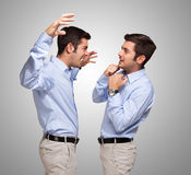 Man attacking a frightened clone of himself. Young man attacking a frightened clone of himself Stock Photos