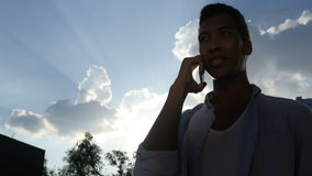 Man Attending Phone Call, in front of Sun during Sunset, Silhouette stock footage