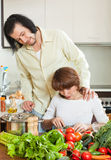 A man and an attractive woman with vegetables in the kitchen Royalty Free Stock Photography