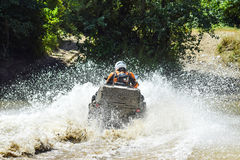 The man on the ATV crosses a stream. Tourist walks on a cross-country terrain Stock Photo