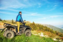 Man on the ATV Quad Bike on the mountains road. Man on the ATV Quad Bike on the mountains road Royalty Free Stock Images