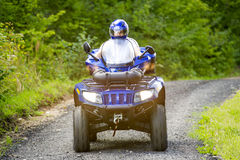 Man on ATV. A man is riding the ATV on the dirt road Royalty Free Stock Image