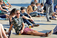 A man from the audience watches a concert and have a beer sitting in the floor Stock Image