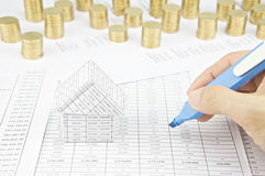 Man is auditing account by highlighter beside house Royalty Free Stock Photo
