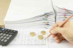 Man auditing account by pencil and gold coins with calculator Stock Photos
