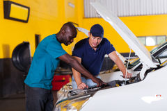 Man auto mechanic. African men showing auto mechanic his car problem inside workshop royalty free stock photos