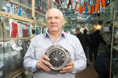 Man   in  auto parts store. Mature man holds  engine clutch  in  auto parts store Stock Photography