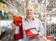 Man  in  auto parts store. Mature man holds  automotive  headlight  in  auto parts store Stock Photography