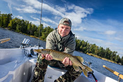 Man with autumn lake pike Royalty Free Stock Photos