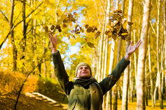 Man and autumn leaves . Young man having fun throwing up piles of autumn leaves Royalty Free Stock Photography