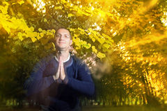 Man in autumn park with namaste greeting Stock Image