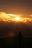 man av att gå för solnedgång Arkivfoto