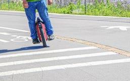 Man av en hjulskateboard som rundar ett hörn på trottoar - personen kantjusteras och har på jeans och teeshirten arkivfoto