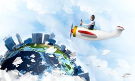 Man in aviator hat with goggles driving plane. Man in aviator hat with goggles driving propeller plane. Earth globe with high modern buildings. Funny man having stock image