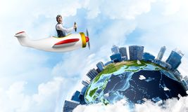 Man in aviator hat with goggles driving plane. Man in aviator hat with goggles driving propeller plane. Earth globe with high modern buildings. Funny man having royalty free stock images