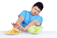 Man avoid junk food. Portrait of man refuse to eat junk food and choose a bow of salad Stock Images
