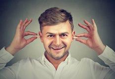 Man avoiding noise with plugs stock image