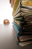 Man Avoiding Work. Bald head of man is visible over top of table in background.  Foreground is a stack of files.  Man appears to be hiding from or trying to Stock Photo