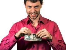 Man avrivning av 20 sedlar för Förenta staternadollar som isoleras på en vit Arkivfoton