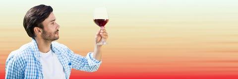 Man avsmakningvin mot oskarp röd och persikabakgrund Arkivfoton