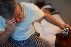 Man Awake In Bed Suffering With Insomnia. Holding Alarm Clock Stock Image