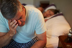 Man Awake In Bed Suffering With Insomnia. Sitting Up With Head In Hand royalty free stock photography