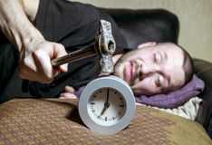 Man awake is trying to break the annoying alarm clock. A man awake is trying to break the annoying alarm clock in the morning royalty free stock photo