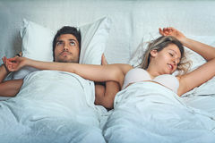 Man awake by woman snoring. Man with funny expression has problem with women snoring Stock Photography