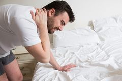 Man suffering from backache getting out of bed Royalty Free Stock Images
