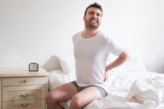 Man awakening in the morning and suffering backache Royalty Free Stock Images
