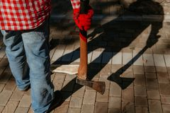 Man with ax gives ominous shadow. Dangerous shadow. A man in a red checkered shirt holds an ax in his hand in the yard. A deceptive shadow falls from him royalty free stock photos