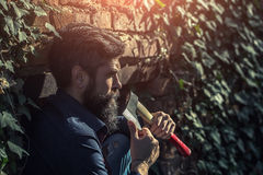 Man with ax near wall. One handsome strong stylish male logger of young man with long lush black beard and moustache in shirt holding wooden axe standing near Royalty Free Stock Images